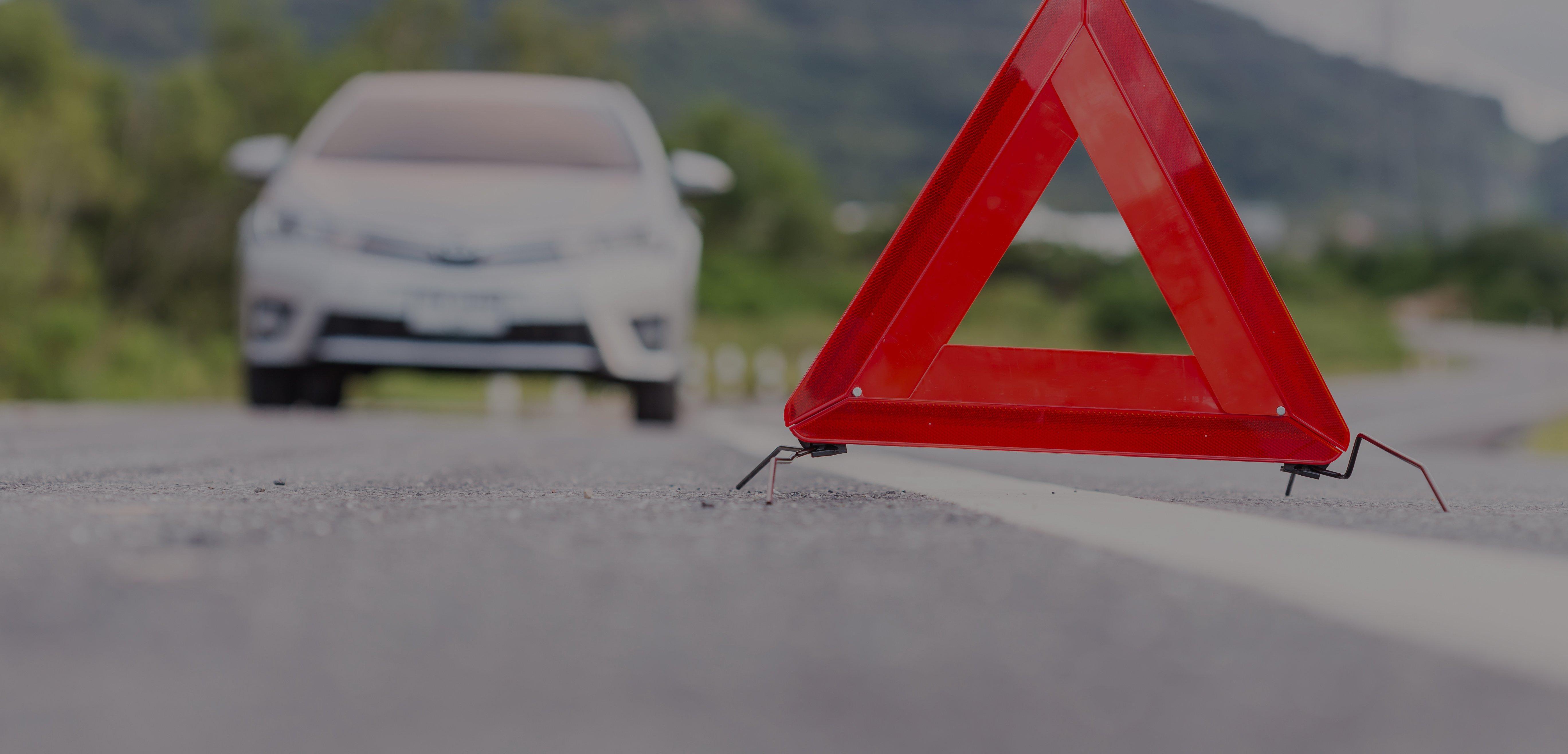 trójkąt odblaskowy ustawiony na środku drogi, za nim samochód